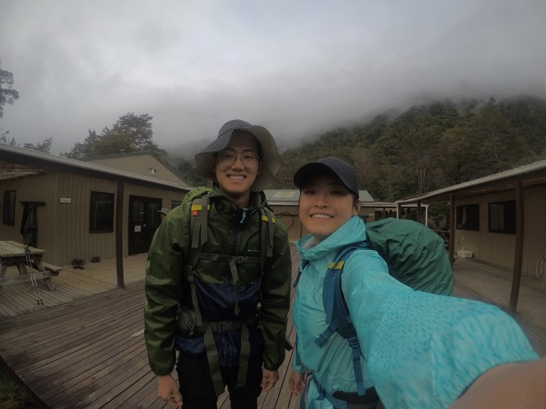 A backpacker couple taking a selfie with clinton hut