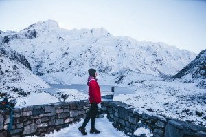 A red jacket lady standing amidst snow and mountains in the distant