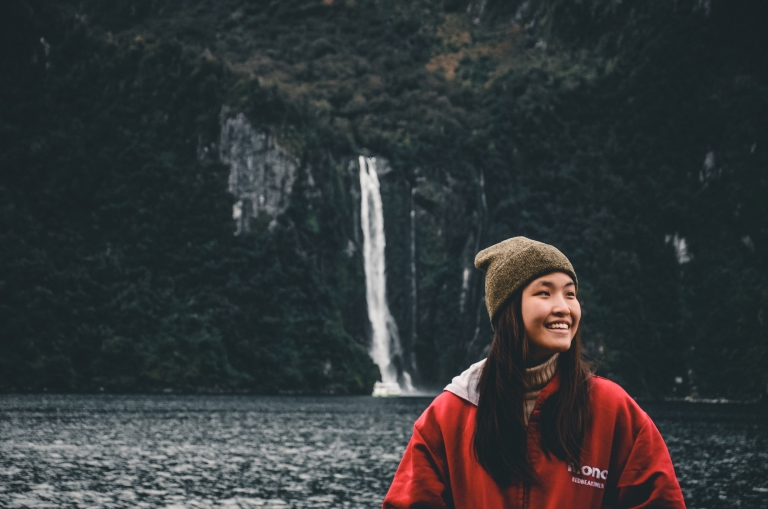 A red jacket beanie girl smiling toward her left with a waterfall crashing down in the distant behind her