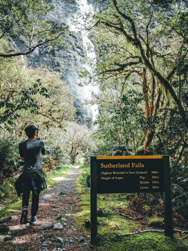 A man backfacing the camera standing beside the Sutherland Falls signboard