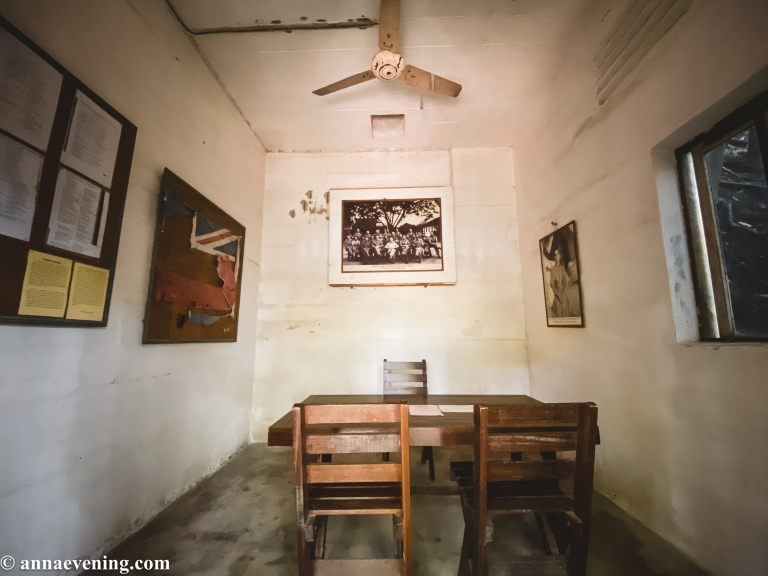 A room with a desk and three chairs and pictures hanging on the wall