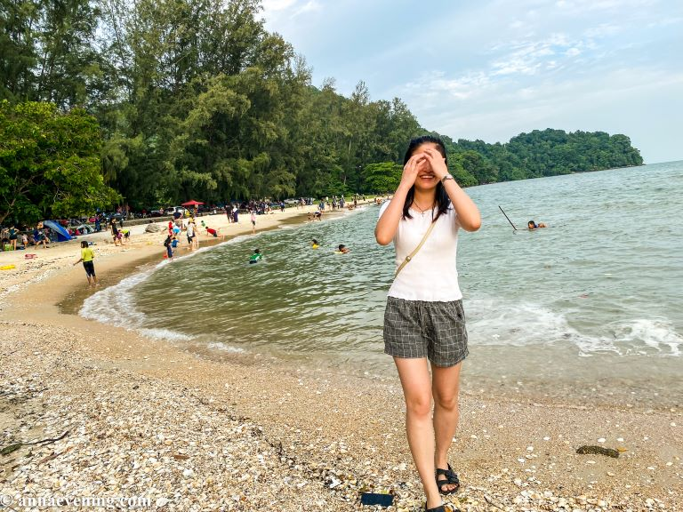 A girl walking toward the camera covering her face on a beach