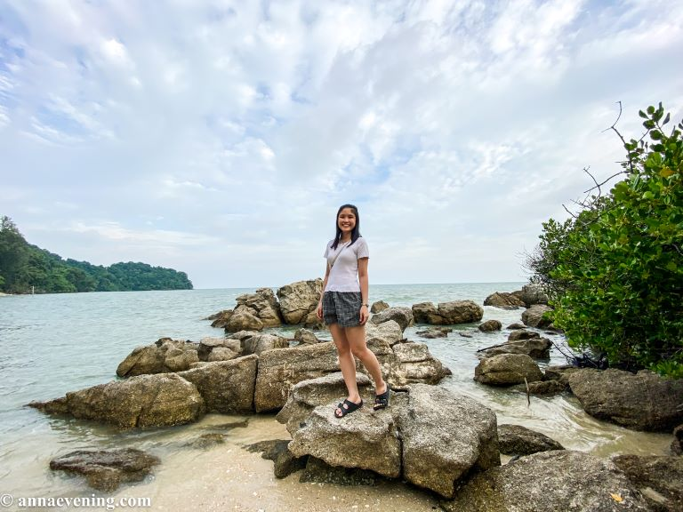 A girl standing on a rock on a beach
