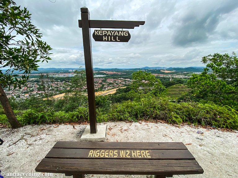 A bench and a sign that says Kepayang Hill with a lookout in front