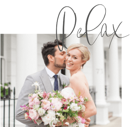 couple photographed in the streets of London holding a large bridal bouquet of peonies and roses