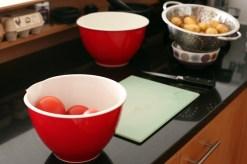 Wash the potatoes and prepare the tomatoes.