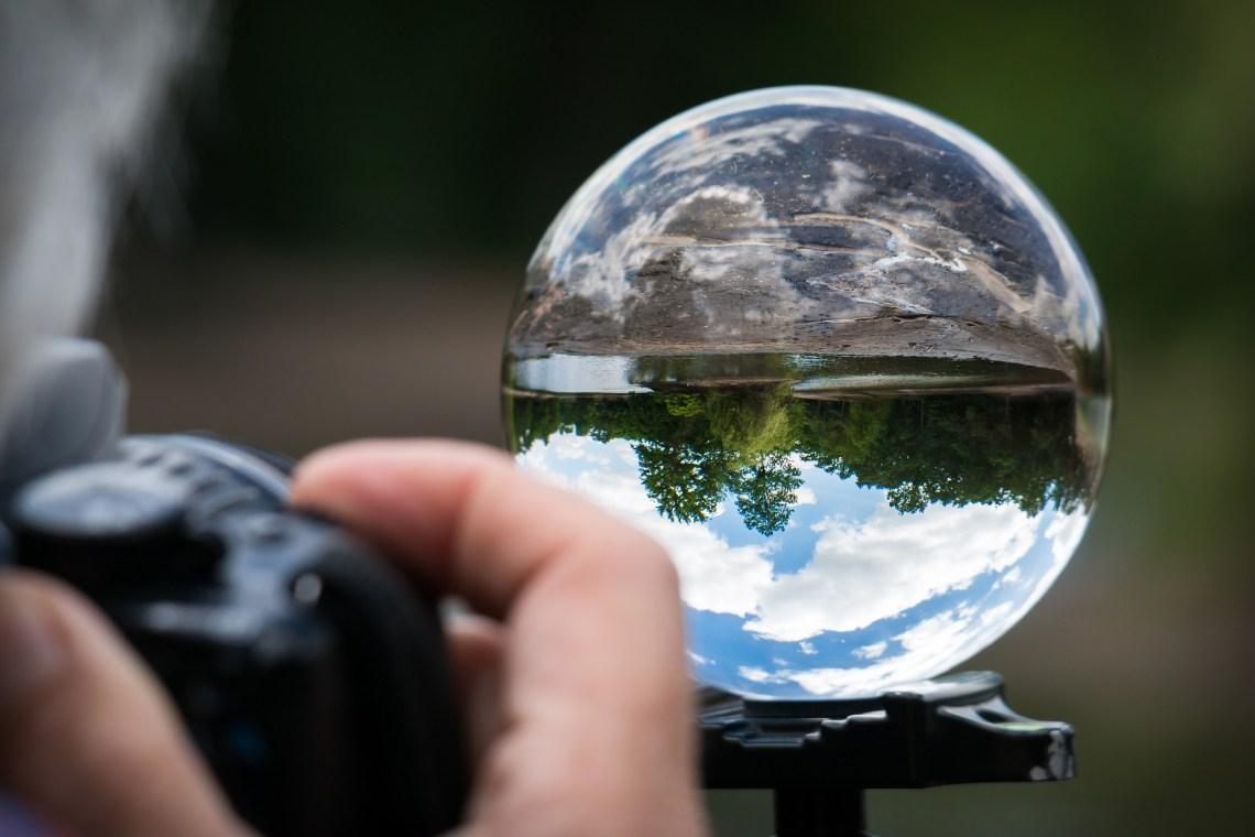 Fotograf fotografiert eine Glaskugel, in der sich Wald und Himmel spiegeln