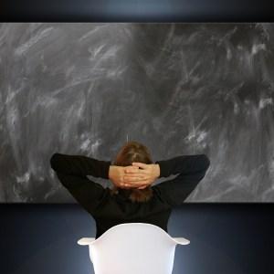 Frau sitzt vor einer leeren Tafel
