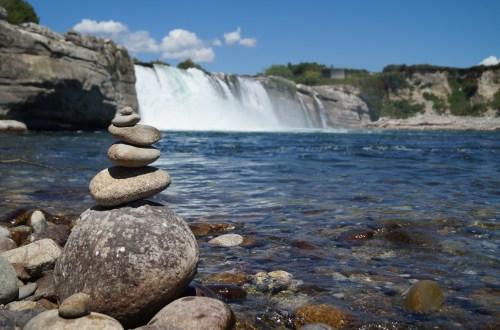 Wasserfall mit einem Steinmännchen im Vordergrund