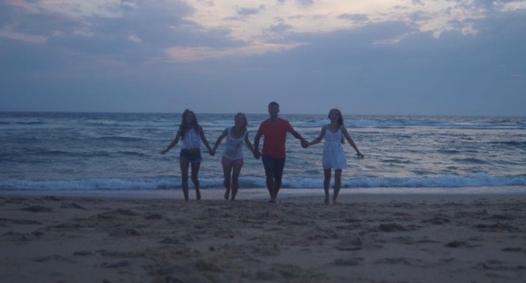 Familie rennt Hand in Hand am Strand entlang