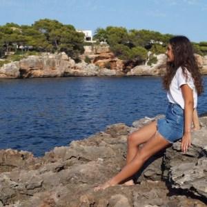 Anna posiert auf einem Felsen am Meer