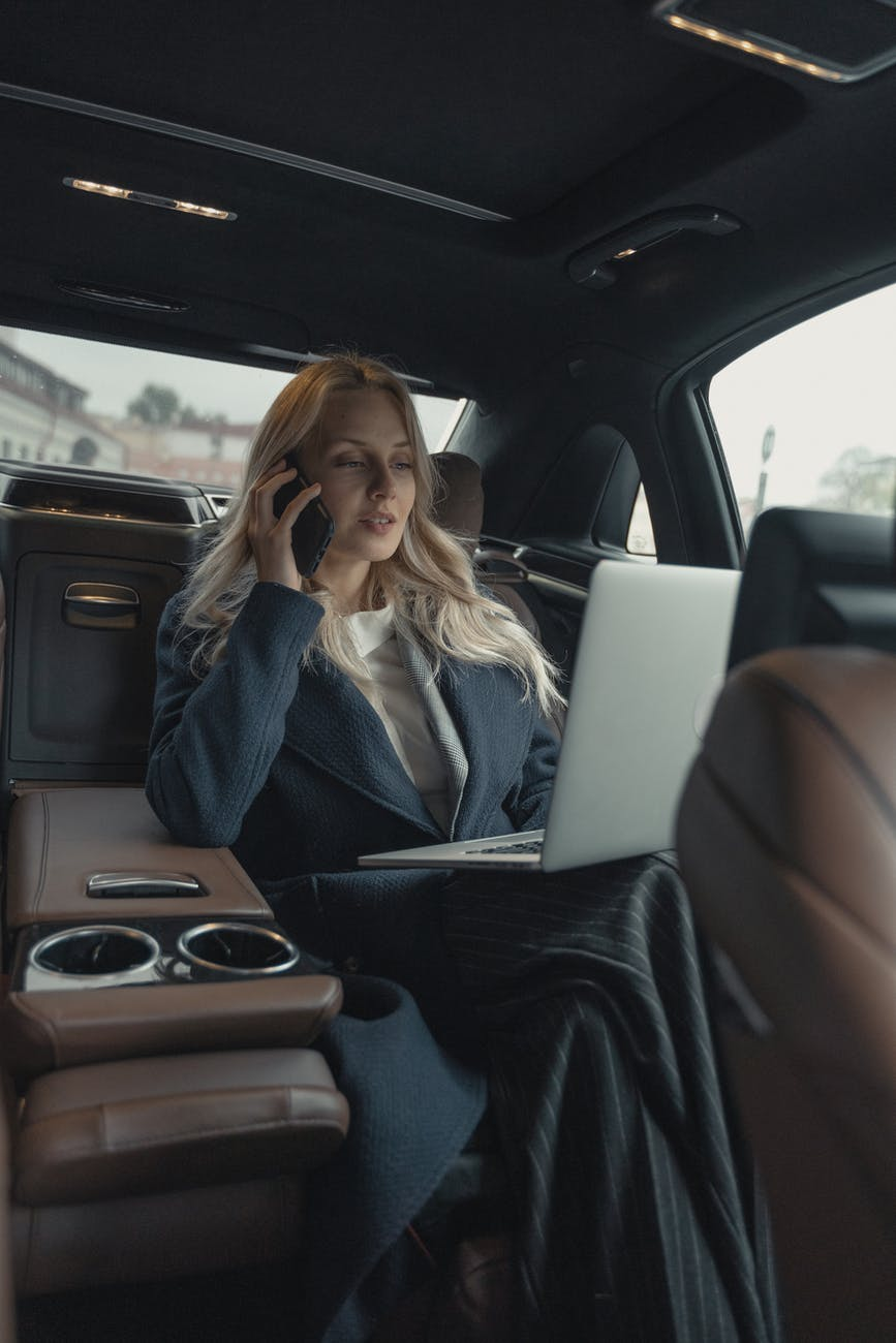 woman in gray business suit sitting in a luxurious fare ride limousine car