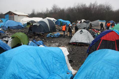 Aid workers clearing up the previous night's fire on the Dunkirk which destroyed 30 tents