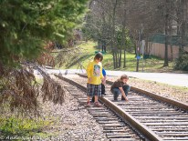 Kids playing on a railroad track.