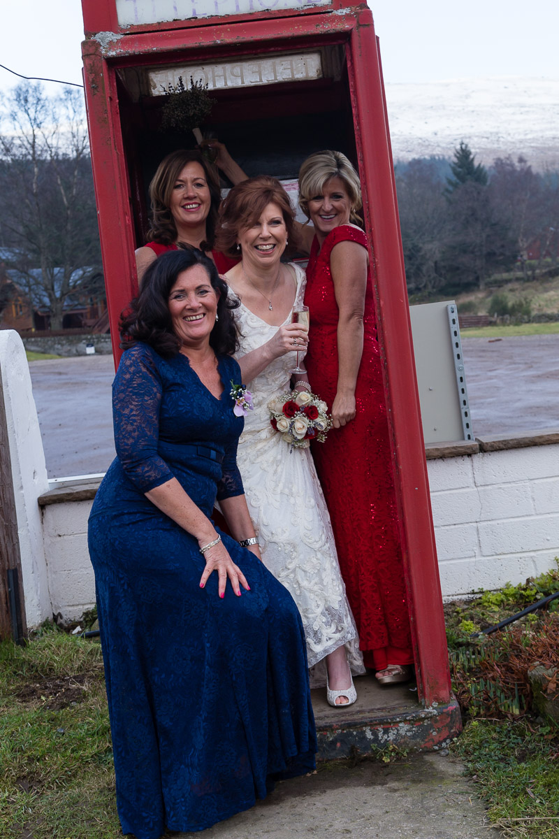 Bride and friends at the red phone box at the Glen Clova Hotel