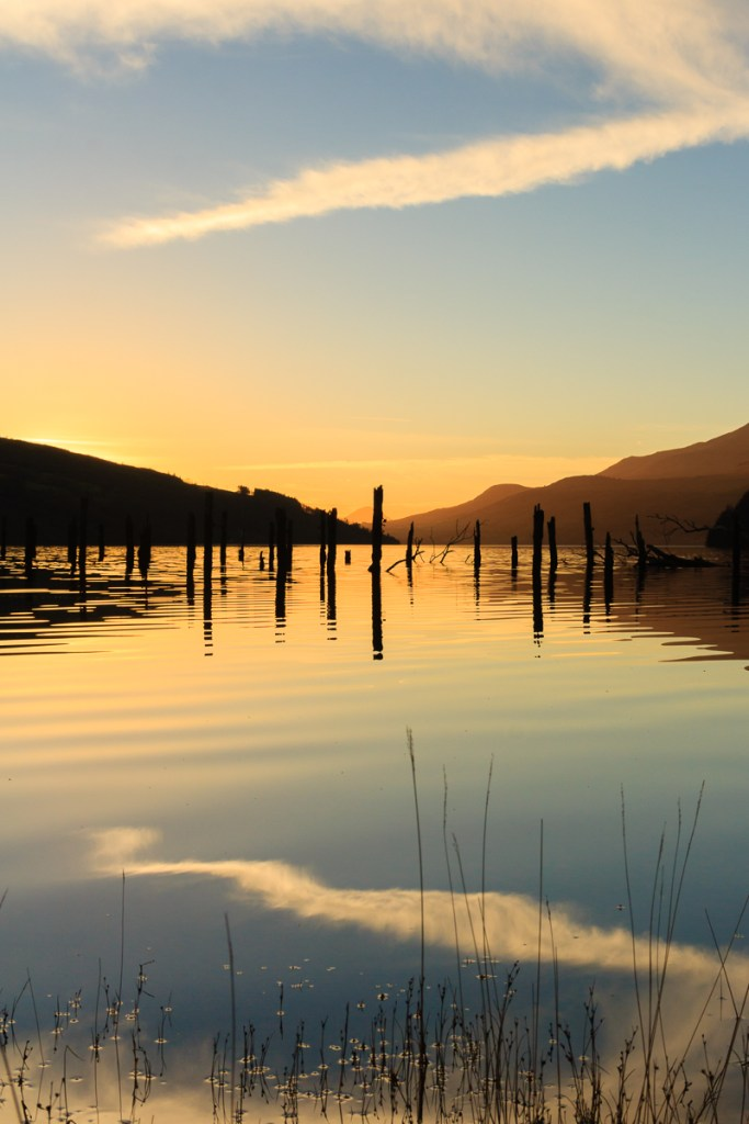 A ruined jetty reflects on Loch Tay at sunset