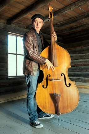 Justin with his bass in a historic cabin.