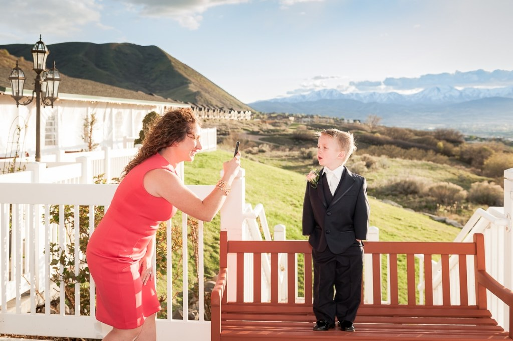 A woman photographs her son with a cell phone at a wedding.