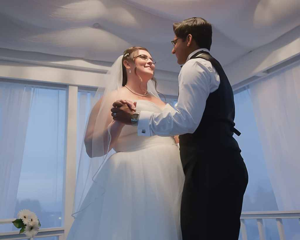 A recently married couple share a private moment dancing inside a gazebo.