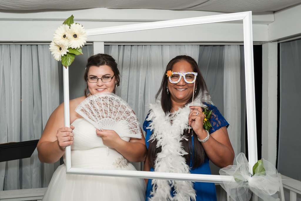 A bride and her mother-in-law share a fun moment in a photo booth with a variety of props.