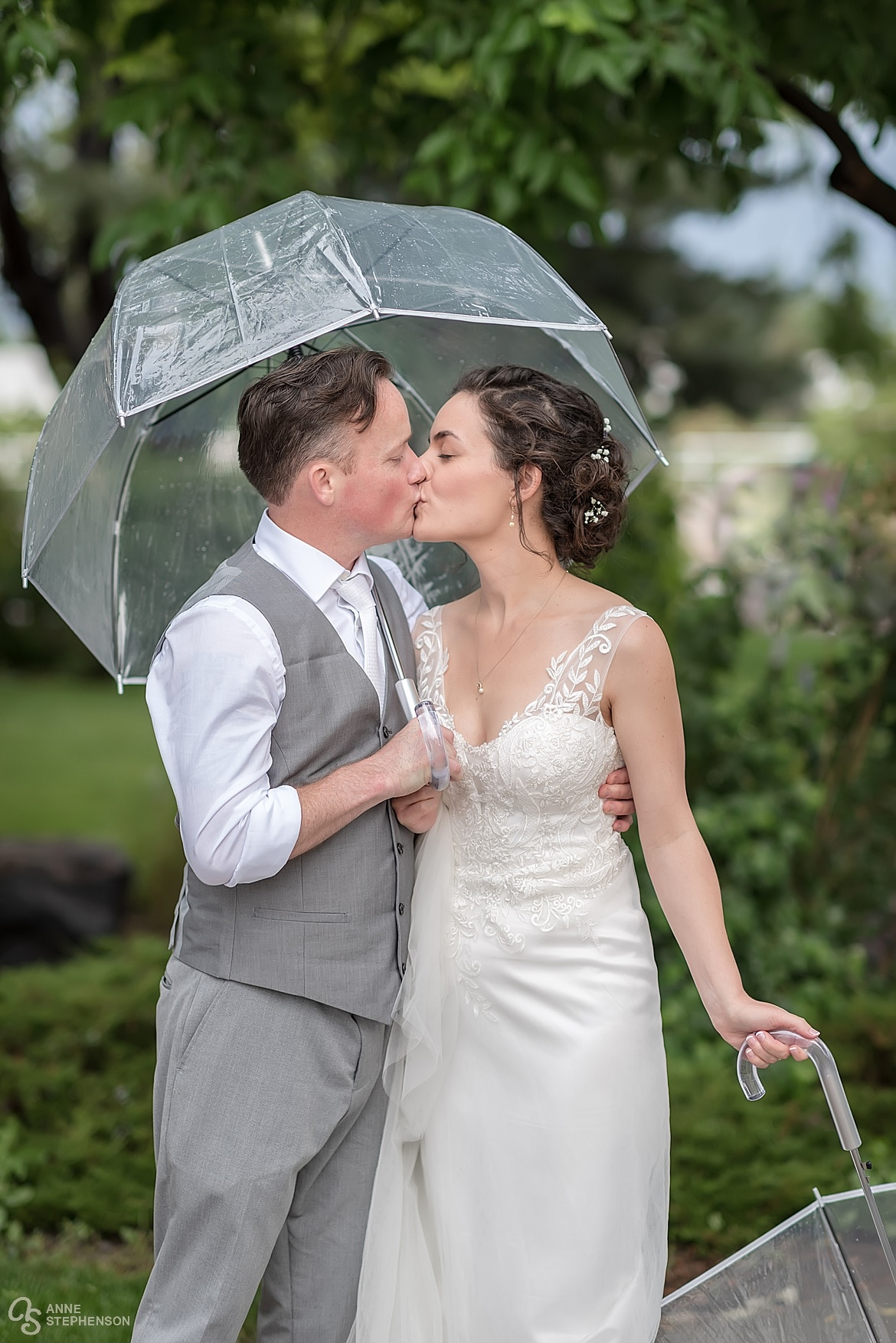 The groom shares his umbrella and a kiss with the bride.