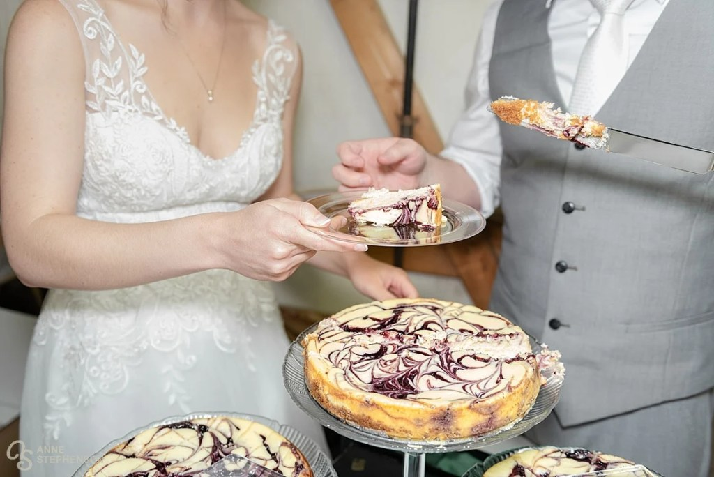 The bride and groom cut the wedding cheesecake.