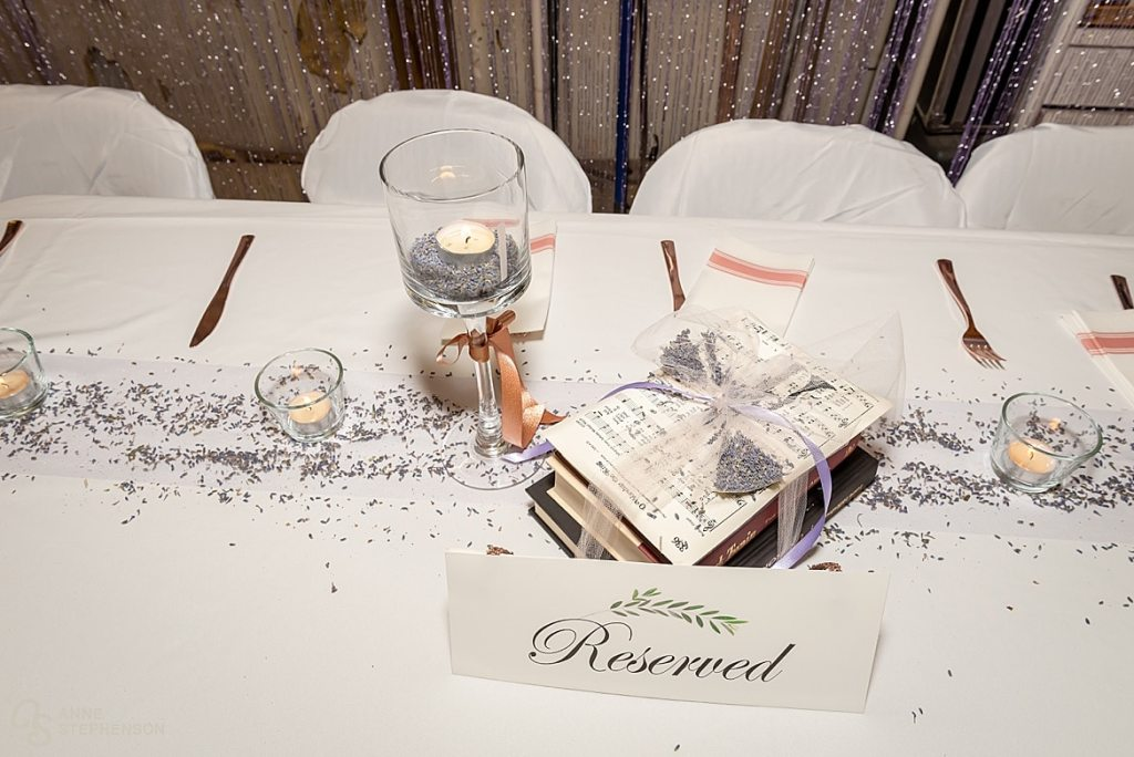 Table decor at the wedding reception includes tea lights, lavender and books wrapped in tulle.