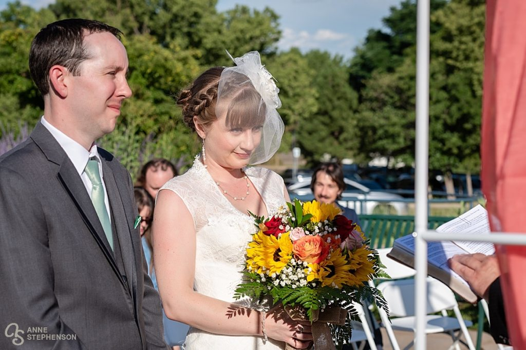 The bride holds a beautiful country bouquet of sunflowers and roses.