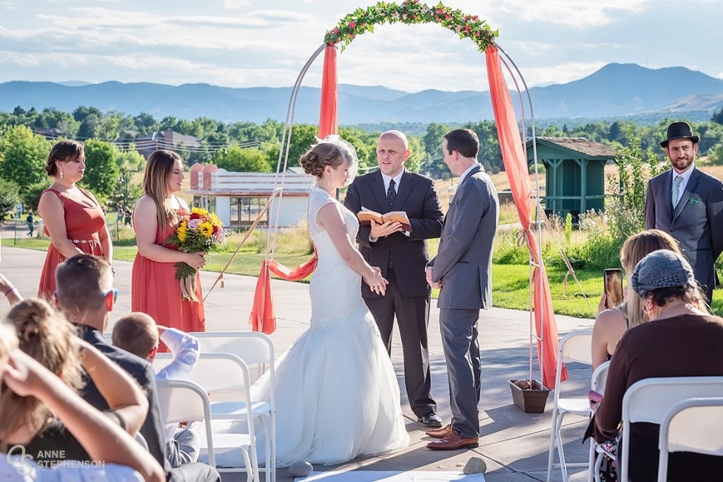A bride and groom stand beneath an arbor and exchange vows at the Lakewood Heritage Center, Lakewood, Colorado.