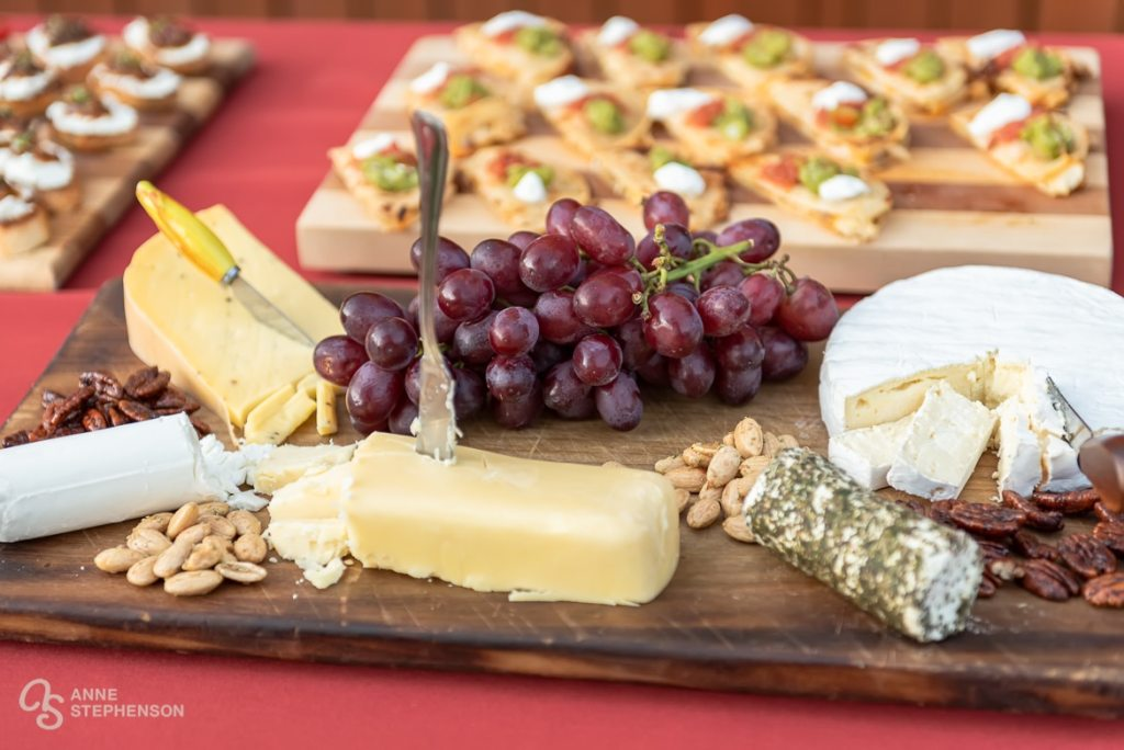 An appetizer plate featuring assorted cheeses, grapes and nuts.