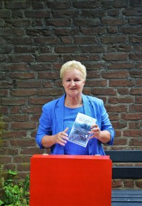 woman standing at a desk holding a book