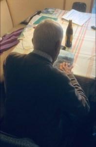 old man looking at book