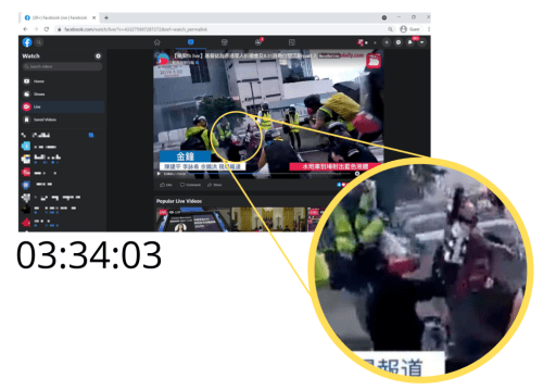 Another screenshot from the Apple Daily livestream at 03:34:03 that zooms into where the protestor is firing the air gun into the air. Photographers from other media outlets are surrounding them taking pictures.