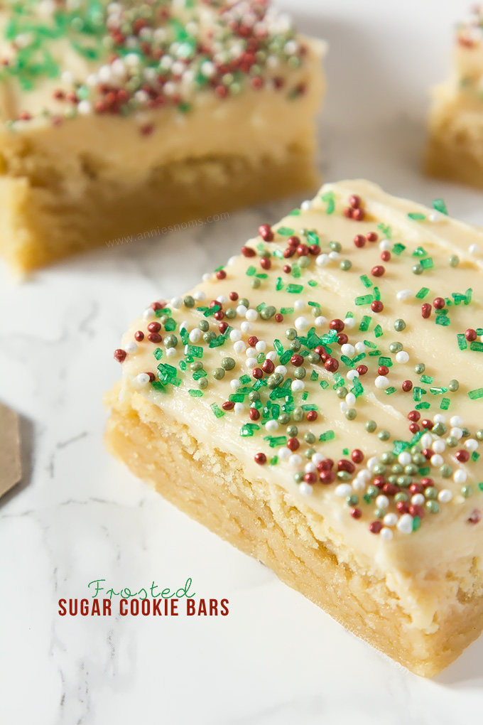 Thick and chewy Sugar cookie dough baked into bars and frosted with velvety smooth buttercream and festive sprinkles!