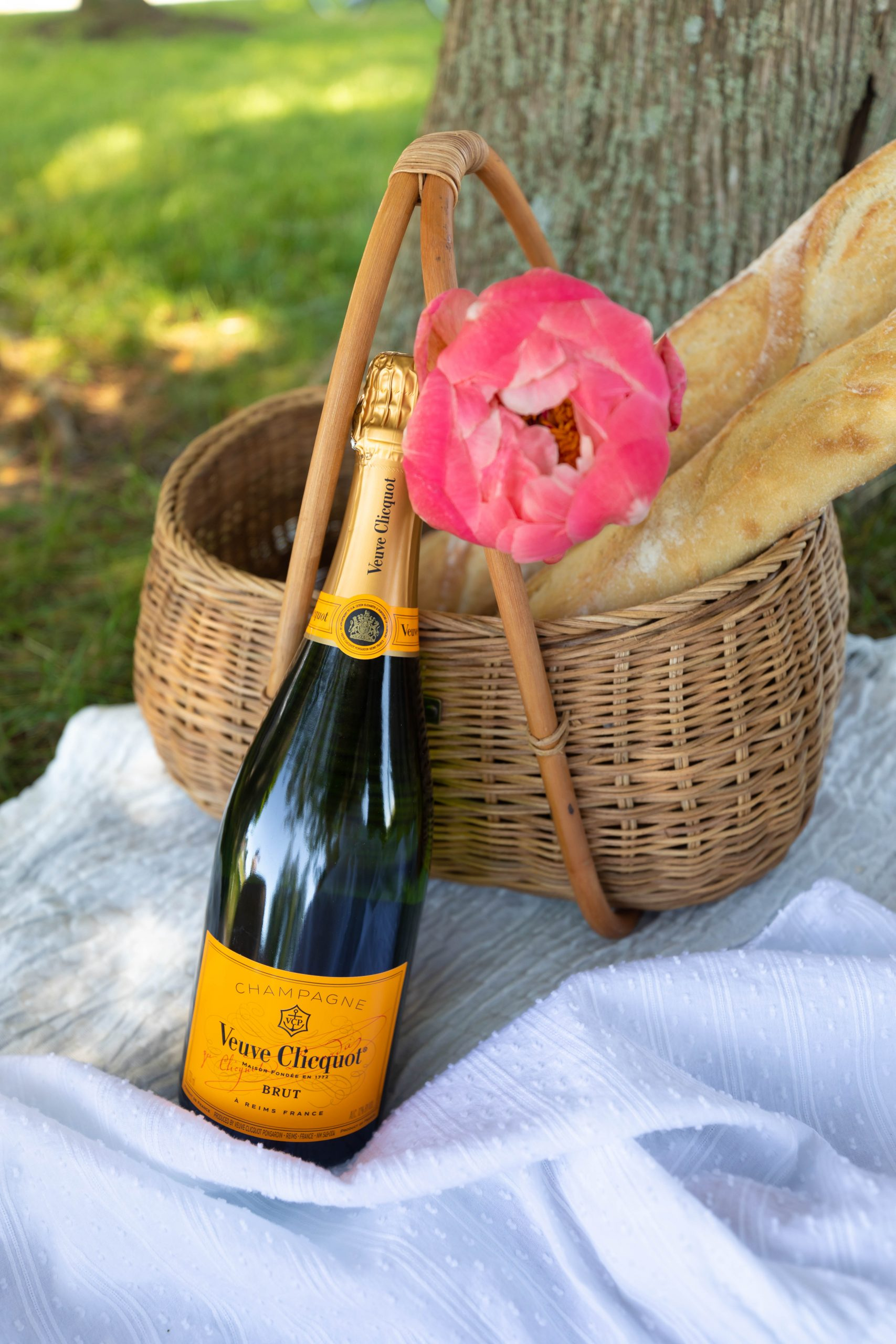 Veuve Clicquot Champagne Ollie Ella Basket with Bageuttes and Peonies Swiss Dot Dress from Duffield Lane by Annie Fairfax