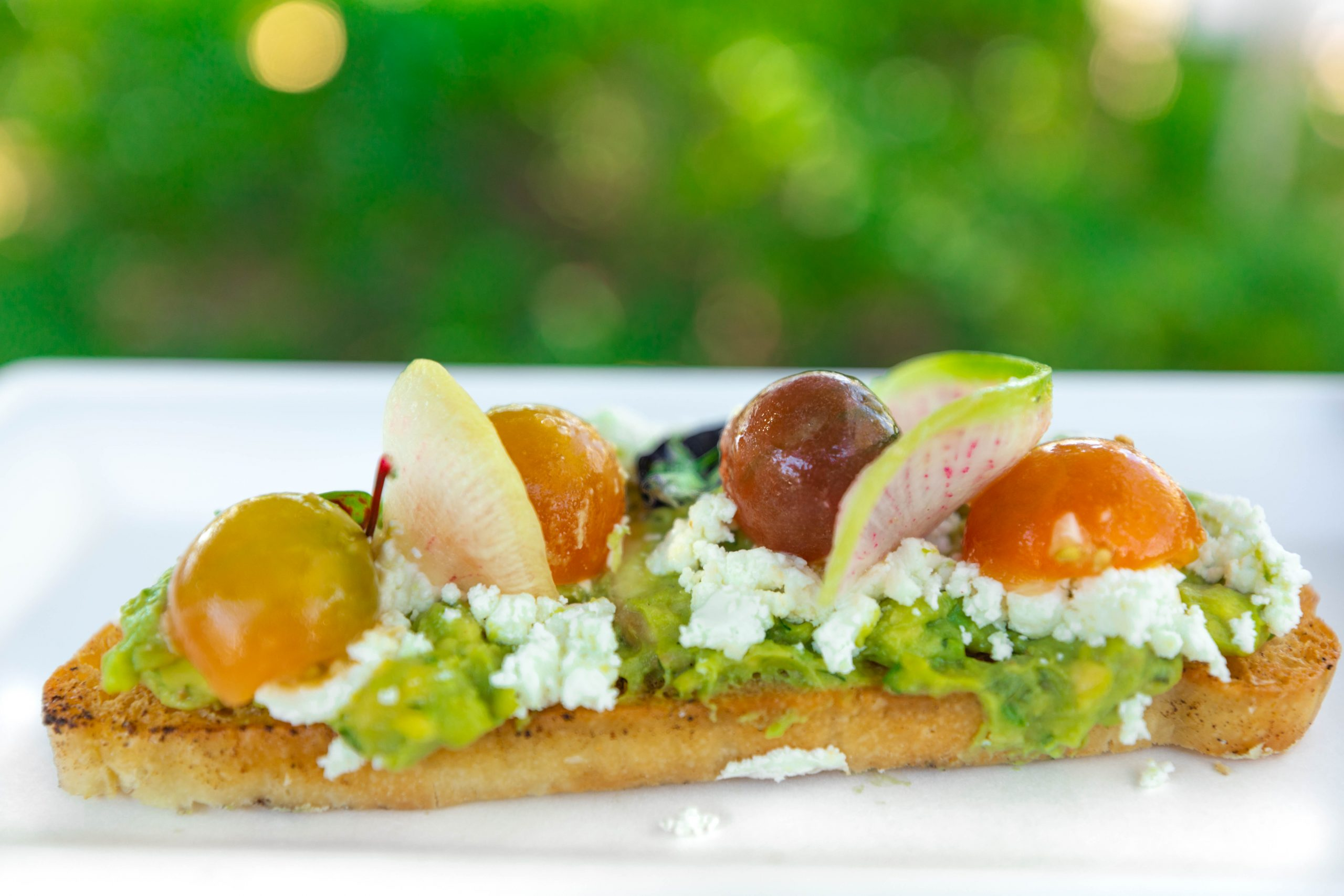 Avocado Toast Marinated toybox tomatoes & fresh goat cheese on toasted ciabatta photographed by Luxury Travel Writer Annie Fairfax Walt Disney World Epcot Food and Drink Guide