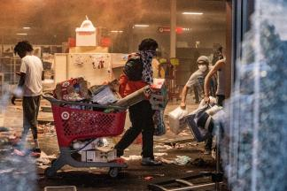 Looters carry out merchandise from the Minneapolis Target on Wednesday. PHOTO BY RICHARD TSONG-TAATARII/STAR TRIBUNE VIA GETTY IMAGES