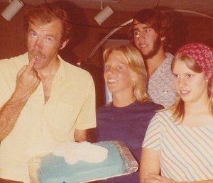 Richard Bach samples the frosting from our seagull cake. Desirei Richards, Kyle Avery, and Wendy Phillips observe.