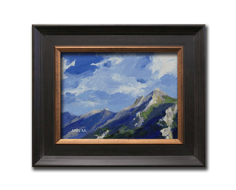 loosely painted mountain art with cloudy blue sky and lavender clouds, shown framed with black moulding and bronze insert