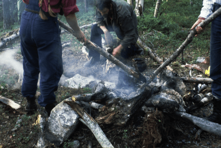 Meat is wrapped in birch bark and placed in a cooking pit. Hot rocks are rolled from the fire into the pit and then covered with moss. Avasjo, Sweden 1982.
