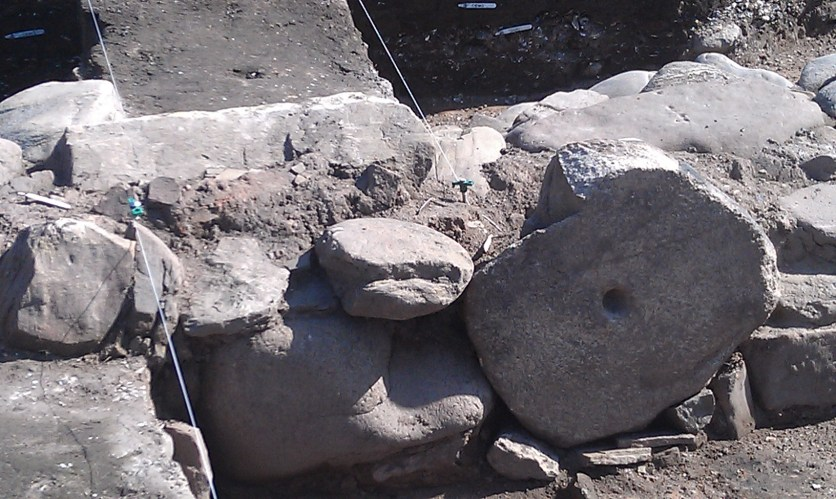 A large lower quernstone has been set into the base of a wall.