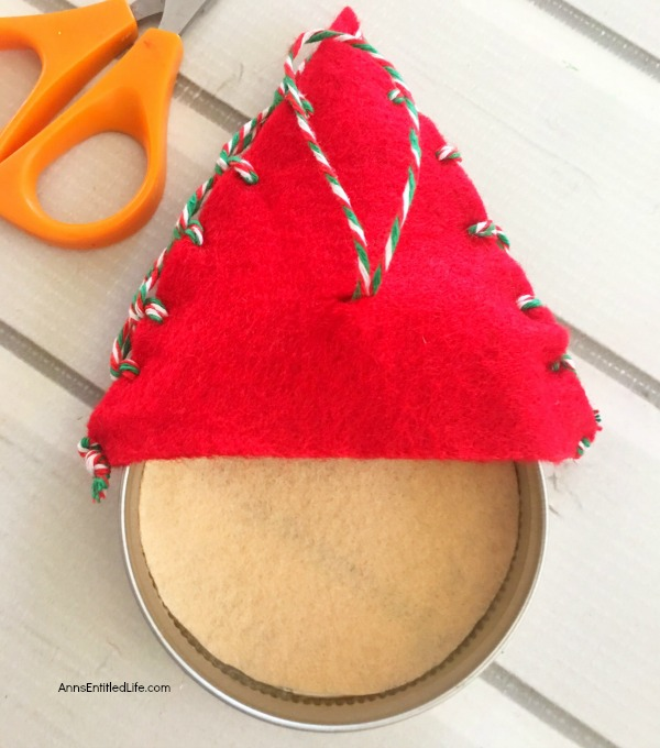 Santa Claus Mason Jar Lid Ornament DIY. Give your Christmas tree a personal touch and make your own ornaments this holiday season. Follow these step-by-step tutorial instructions to make this adorable Santa Claus Mason Jar Lid Ornament!