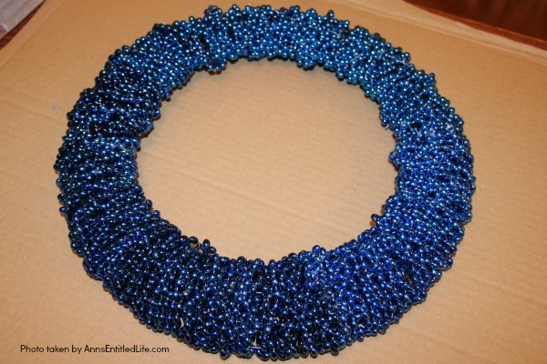 Snowflake Bead Wreath Craft DIY. This is a beautiful snowflake wreath that is perfect for door decor in the chilly winter months. You can fully customize this snowflake bead wreath for color, and ornaments. Simple to make, this lovely Snowflake Bead Wreath Craft is a real conversation piece.