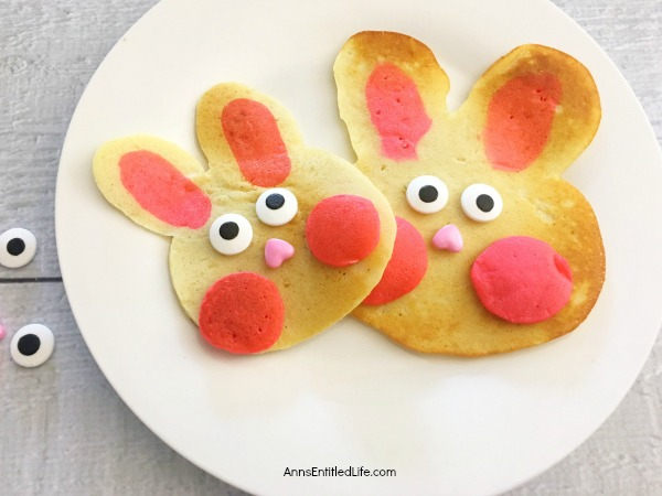 pancakes made in the shape of a rabbit head, decorated as bunnies on a white plate