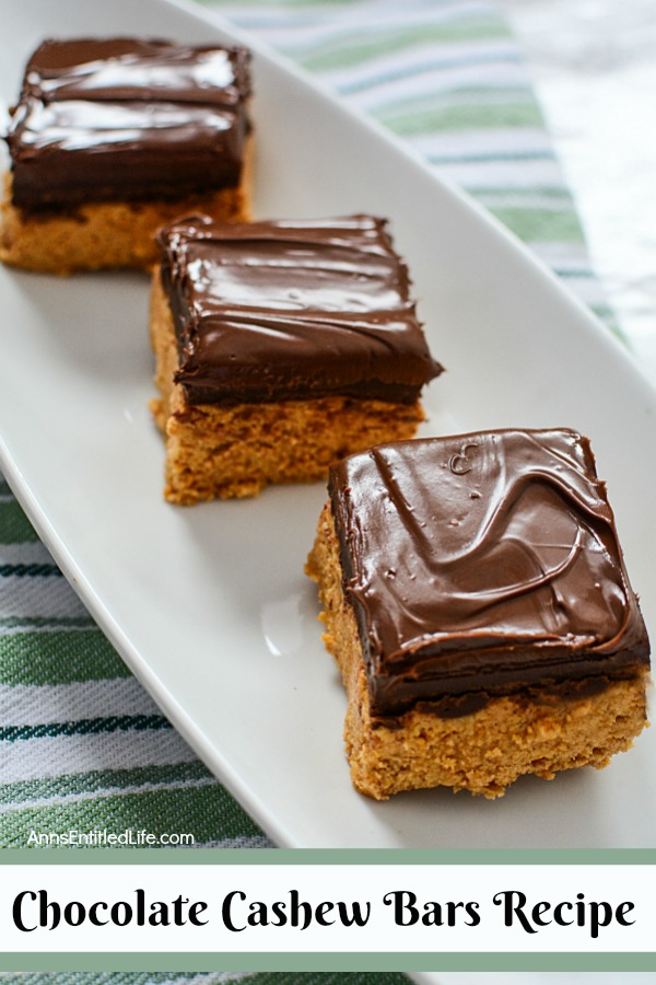 three cashew cookie bars topped with chocolate on a white serving dish on top of a green striped dishtowel