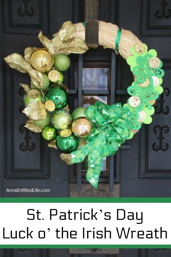 straw wreath decorated for st patrick's day with green and gold bulbs, green ribbon, and gold coins, hanging on a bronze door hanger on a dark colored door