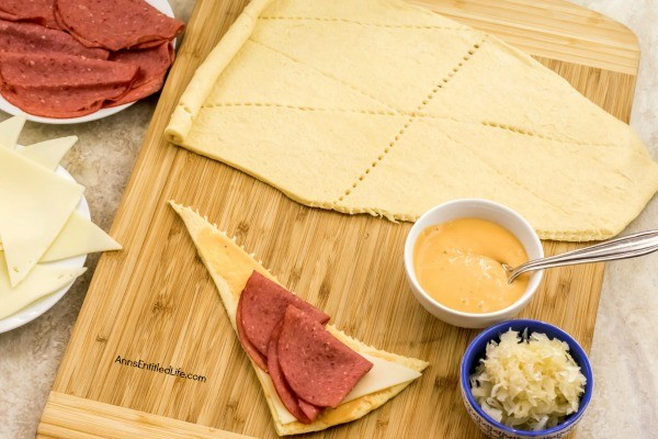 Reuben Crescent Rolls Recipe. These delightful little rolls are a fantastic combination of corned beef, Swiss cheese, sauerkraut, and Thousand Island dressing for a new version of the old favorite deli sandwich. These Reuben crescent rolls are wonderful for serving as an appetizer, snack, or enjoying two or three for your lunch!