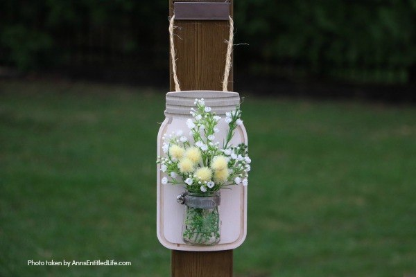 Farmhouse Décor: Jar Flower Holder. This adorable little jar flower holder is easy to make, rustic decor. Great indoors or outdoors decorating, this sweet little bud vase fills in that small section of open wall space perfectly. The step-by-step tutorial will show you how to make this simple DIY farmhouse décor jar flower holder inexpensively.