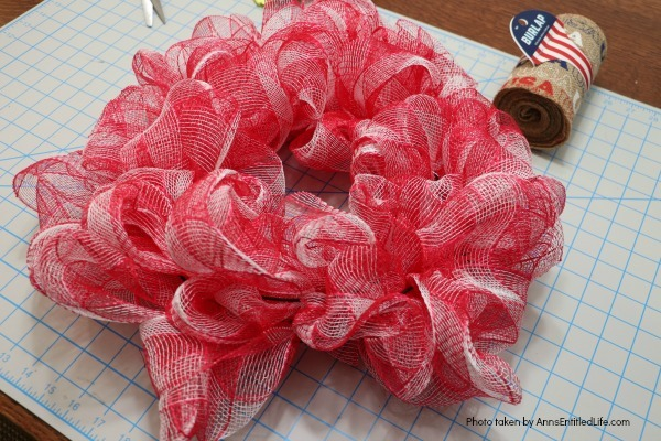 Patriotic Farmhouse Wreath DIY. This simple to make, rustic style American patriotic mesh farmhouse wreath is wonderful for outdoor or indoor display. Using only three materials and scissors, this easy to make wreath comes together in about 15 minutes. If you are looking for a patriotic holiday wreath, this little beauty is it!