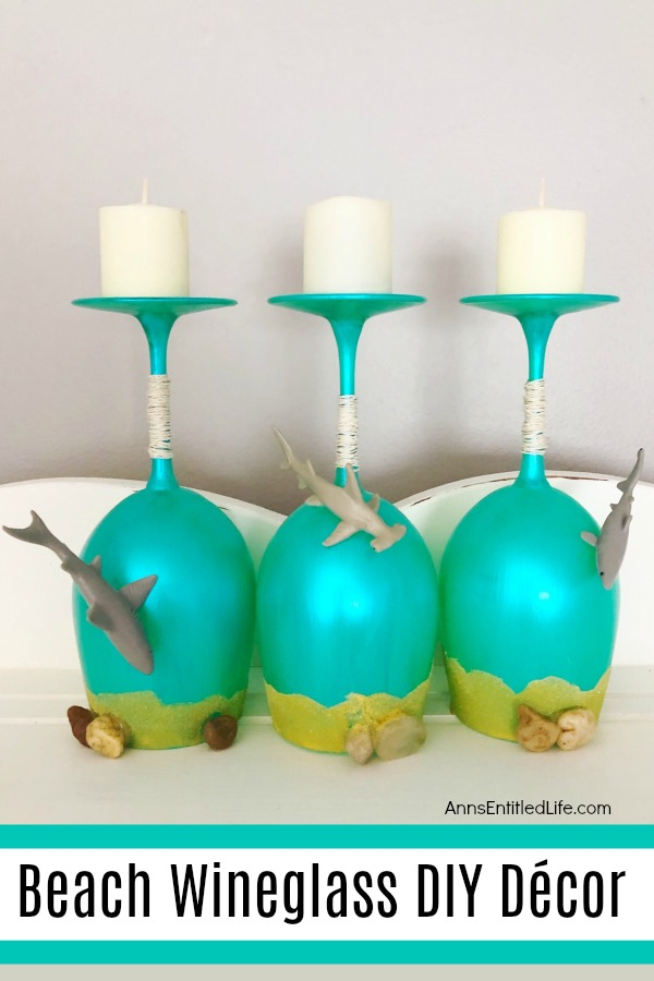 aqua painted wineglasses, upside down, with sand and pebbles embellishments on a grey background